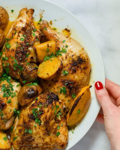 Overhead view of roasted paprika chicken and potatoes garnished with parsley on a white plate.