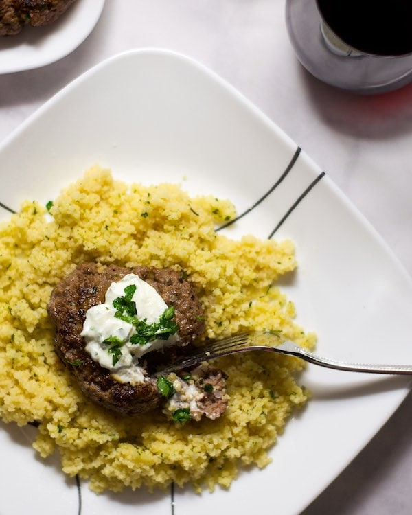 Overhead shot of a fork dipping into a cooked ground beef hamburger patty on top of cous cous, topped with herbed yogurt on a white plate.