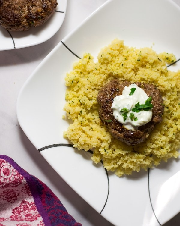 Overhead shot of a cooked hamburger patty on top of cous cous, topped with herbed yogurt on a white plate.