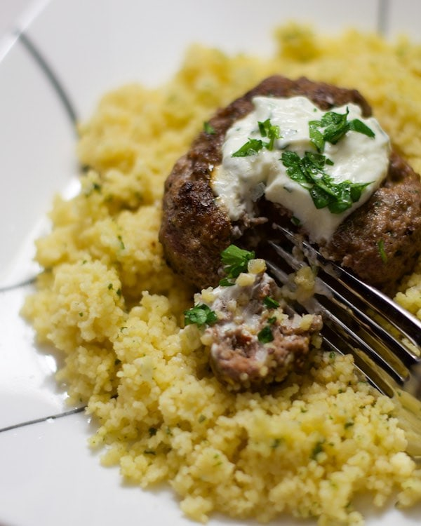 Up close shot of fork dipping into a ground beef burger patty on top of cooked cous cous on a white plate, topped with herbed yogurt.