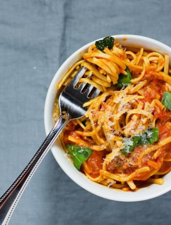 Overhead shot of a bowl of tomato basil pasta with a silver fork.