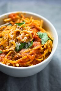 Side view of a bowl of tomato basil pasta.