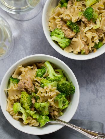 Overhead view of two bowls of sausage and broccoli pasta with two glasses of white wine.