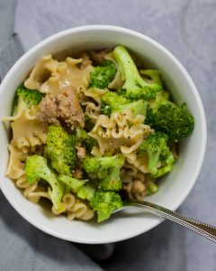 Overhead view of sausage and broccoli pasta in a white bowl.