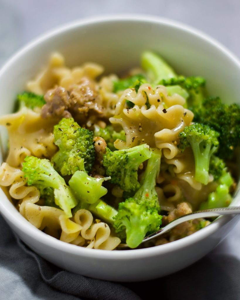 Up-close view of sausage and broccoli pasta in a white bowl.