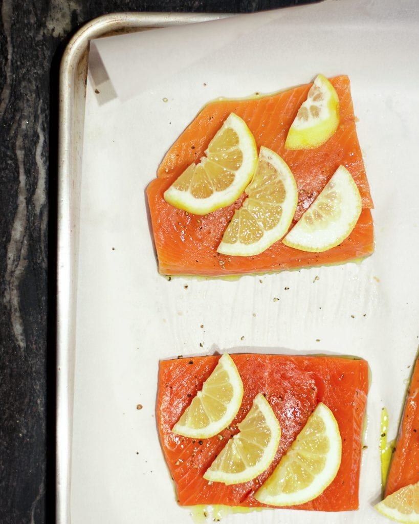 Overhead image of uncooked salmon fillets on a parchment-lined sheet pan topped with lemon slices.