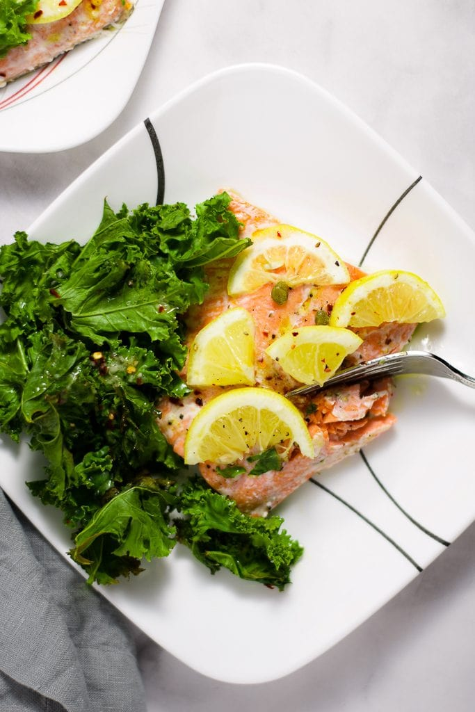 Overhead shot of roasted salmon with lemon slices, roasted kale, and capers on a white plate with a silver fork.