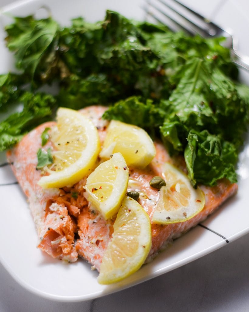 Up-close and side view of roasted salmon with lemon slices, roasted kale, and capers on a white plate.
