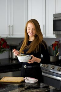 Redhead woman standing at a kitchen counter in the daylight with a bowl of food.