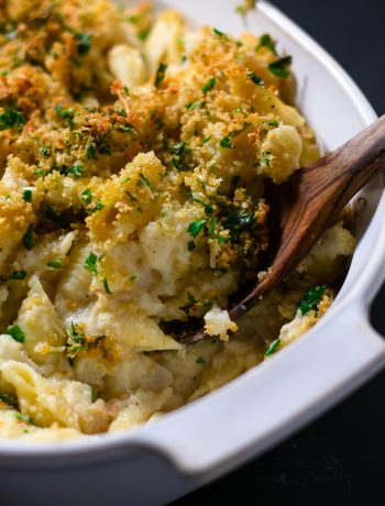 Close-up view of healthy baked pasta with cauliflower sauce with a wooden spoon dipping into it from the right.