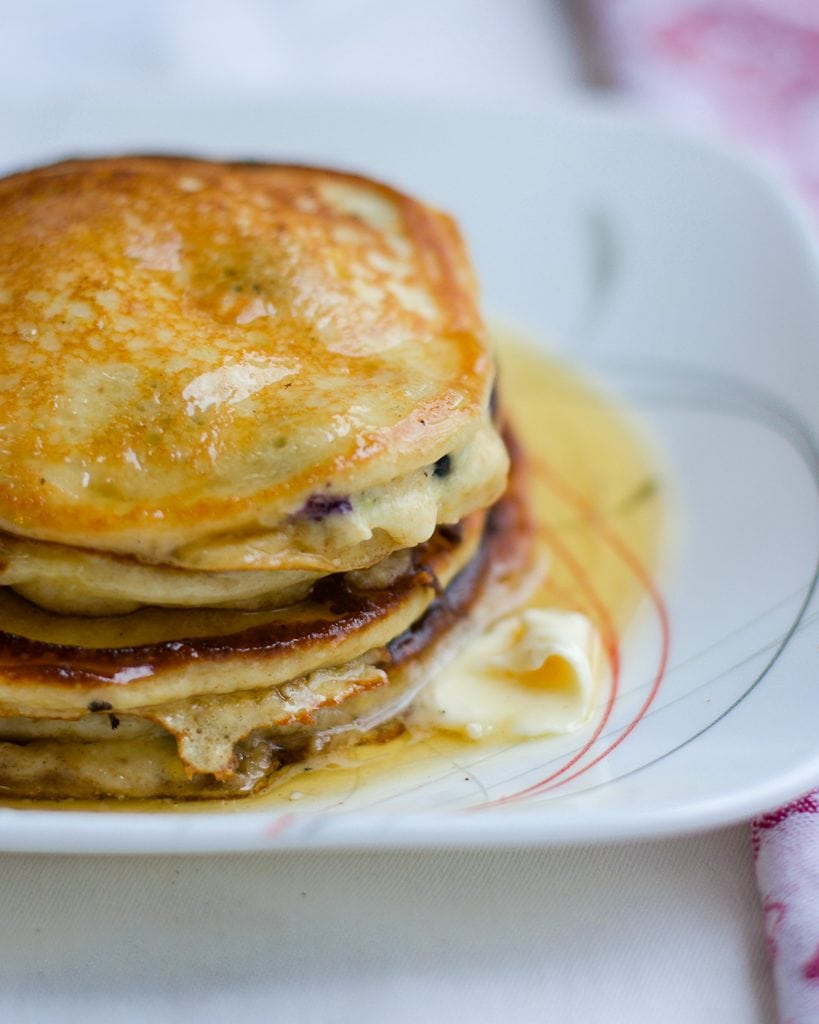 Up-close and side view of a stack of blueberry pancakes on a white plate.