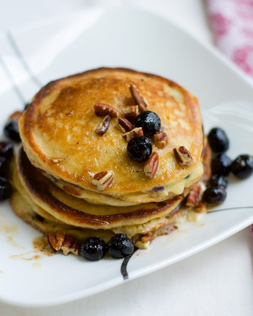 A stack of blueberry pancakes topped with fresh blueberries and pecans on a white plate.