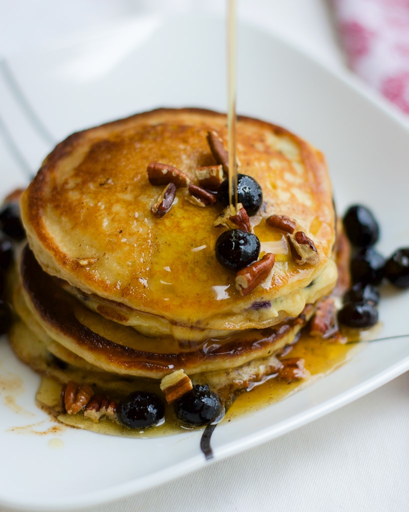 A stack of blueberry pancakes topped with fresh blueberries and pecans on a white plate with maple syrup.