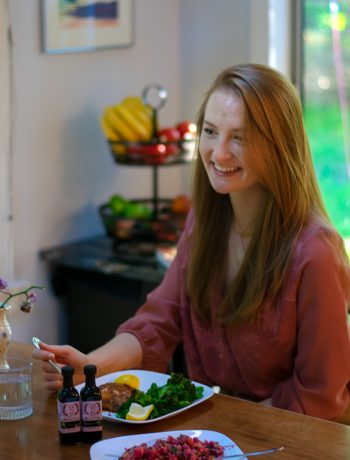 Woman sitting at a kitchen table smiling and eating dinner.