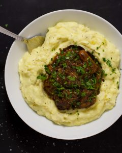 Overhead shot of a silver spoon dipping into a white bowl of mashed potatoes and short rib.