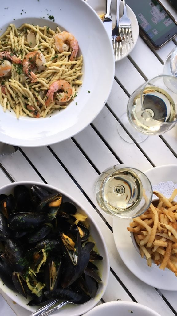Overhead shot of a bowl of mussels and a bowl of spaghetti with two glasses of wine on a white table.