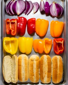 Overhead shot of a sheet pan with bell peppers, onions, and hot dog buns.