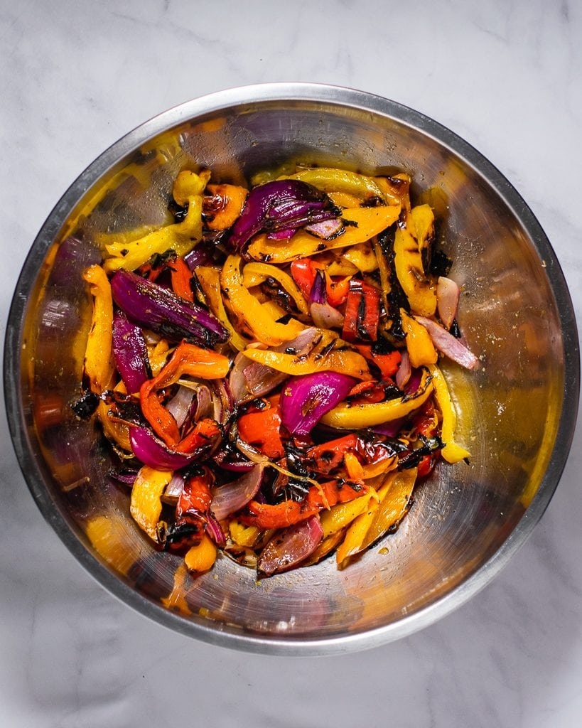 Overhead shot of a bowl of grilled peppers and onions.