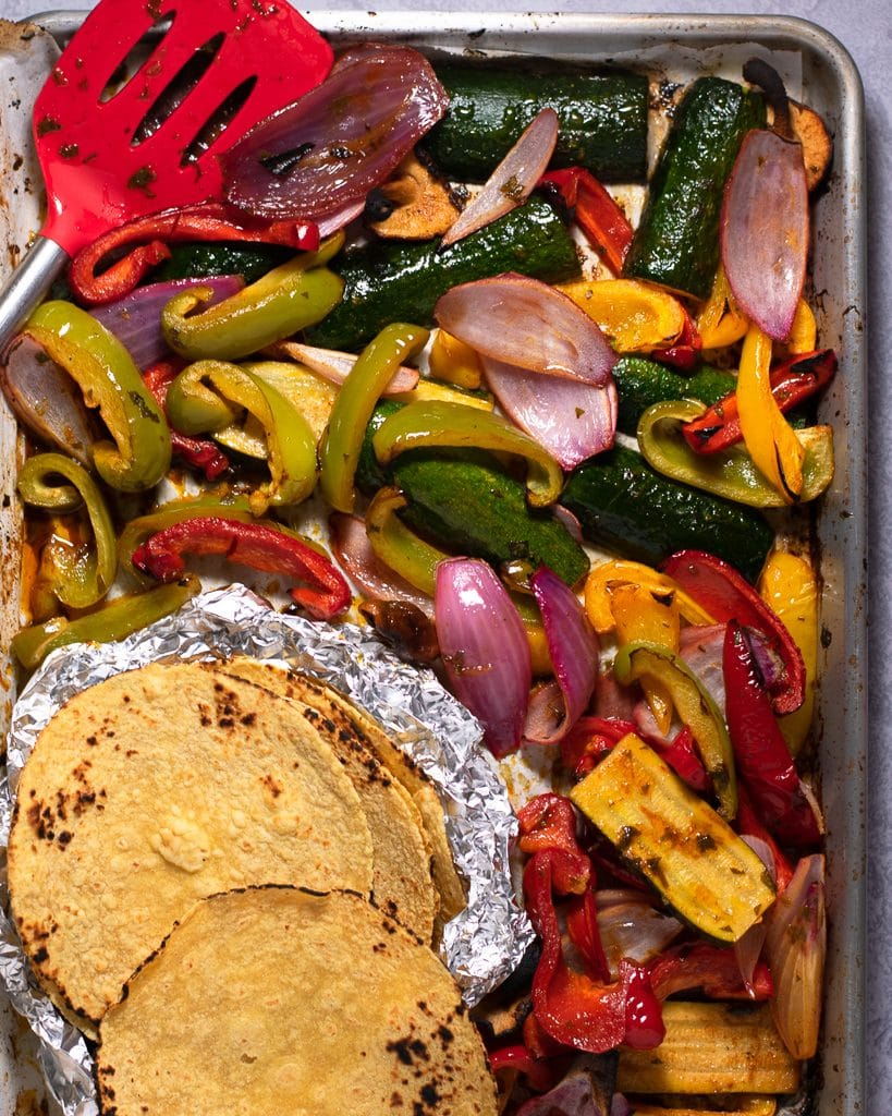 Overhead shot of grilled vegetables and tortillas on a sheet pan with a red spatula.