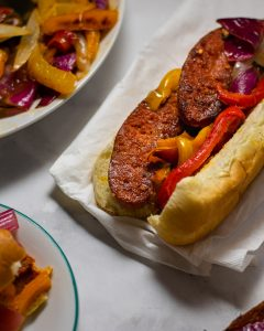Grilled sausages in a soft bun with grilled peppers and onions.