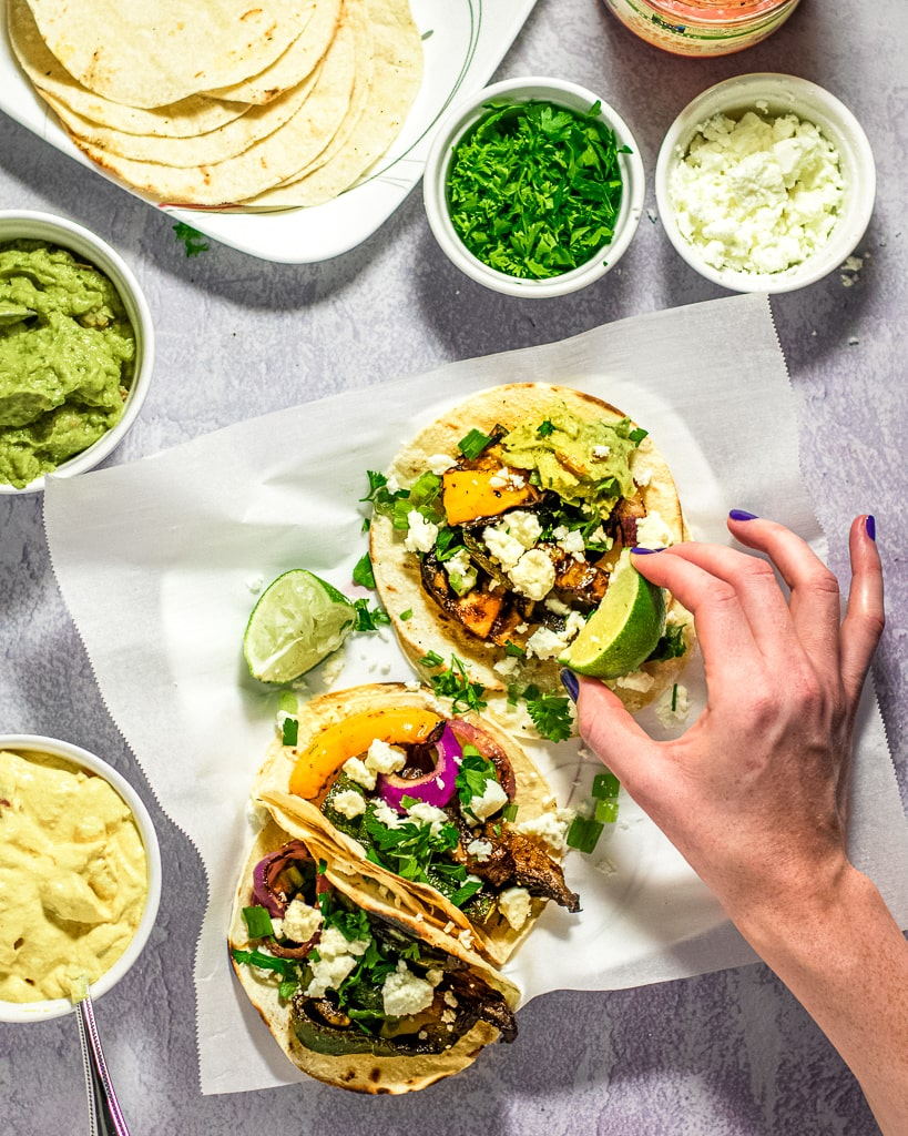 Grilled Vegetarian Tacos with hand squeezing lime