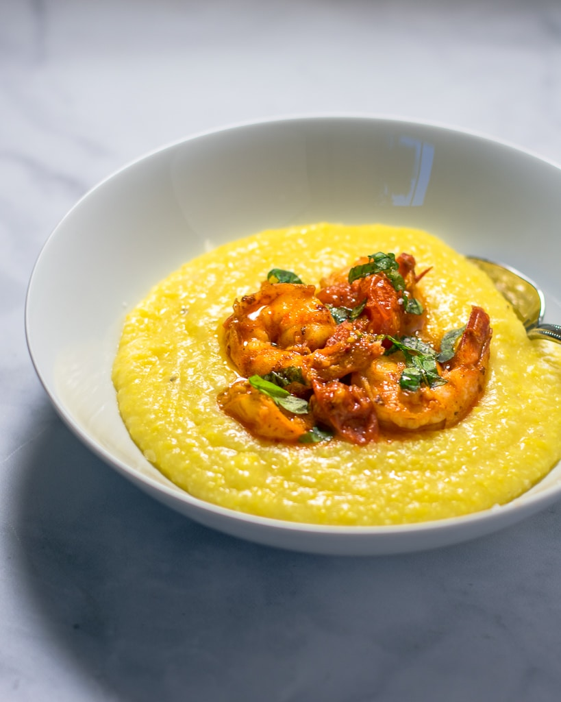 Shrimp and polenta with tomato sauce in a white bowl.