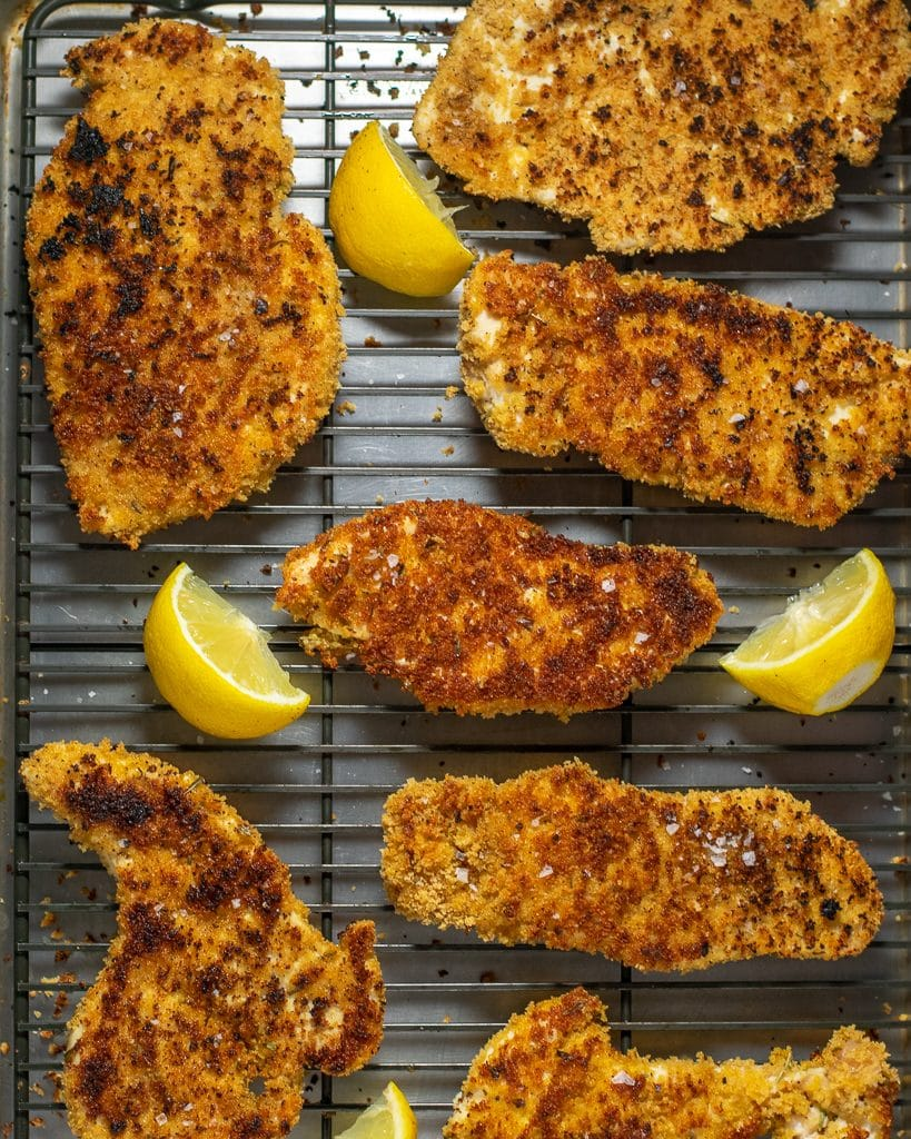 Six breaded chicken cutlets on a wire-rimmed sheet pan with three lemon wedges.