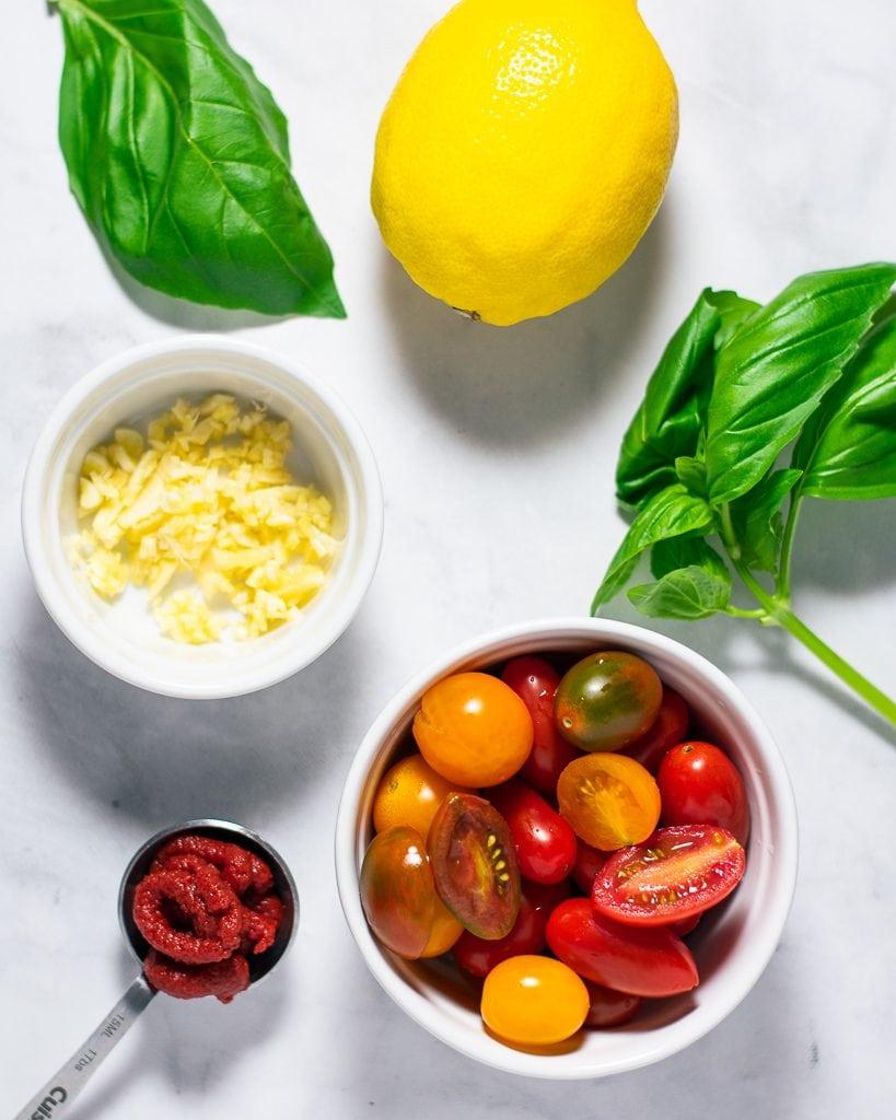 Flatlay of basil, lemon, cherry tomatoes, tomato paste, and garlic