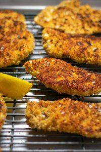Crispy chicken cutlets and a lemon wedge on a baking sheet lined with a wire rack.