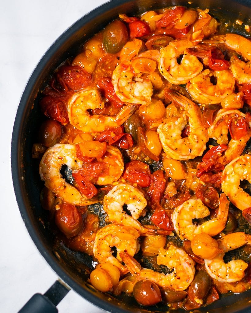 Seared shrimp and cherry tomato sauce in a black skillet