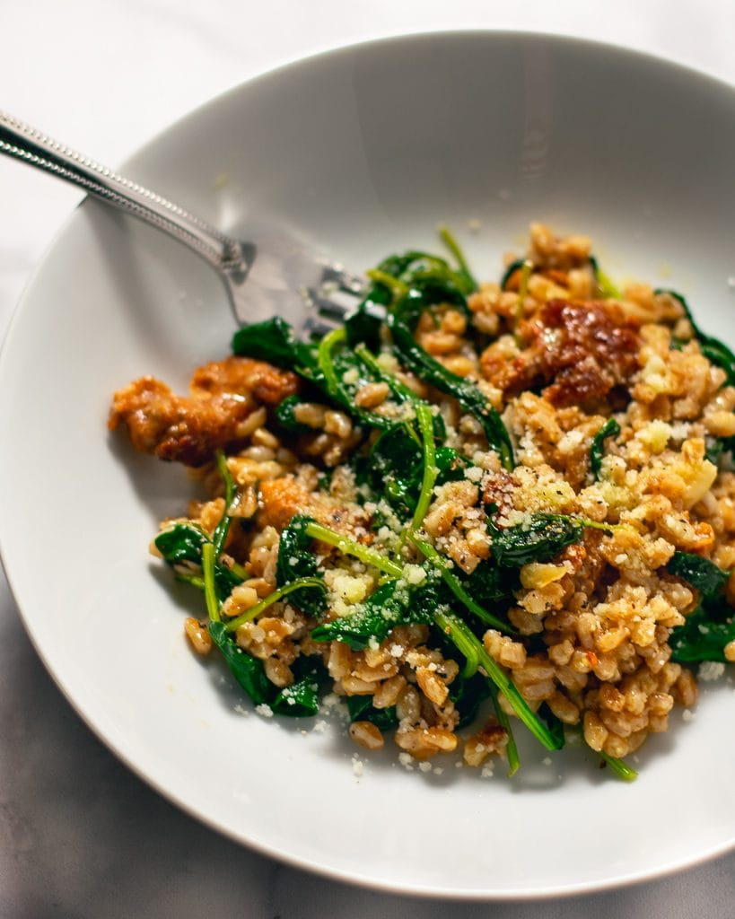 Farro with sausage and kale in white bowl with a silver spoon