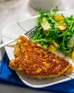 Crispy chicken cutlets on a white plate with a green salad.