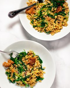 Farro with sausage and kale in two white bowls with a silver fork in each bowl.