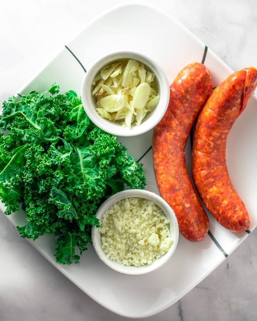 Sausage, kale, garlic and pecorino on a white plate.