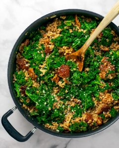 Farro with sausage and kale in one skillet with a wooden spoon.