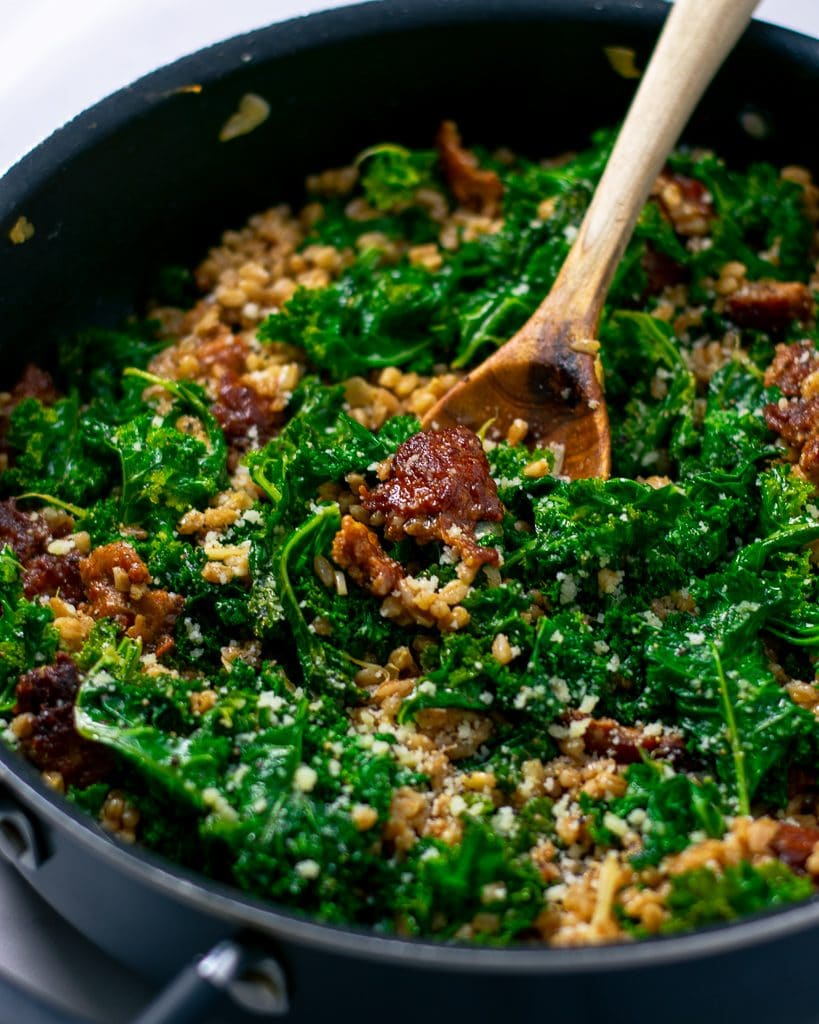 Close-up shot of farro with sausage and kale in one skillet with a wooden spoon