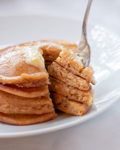 Stack of whole wheat pancakes with a bite taken out of it and a fork going into the stack.