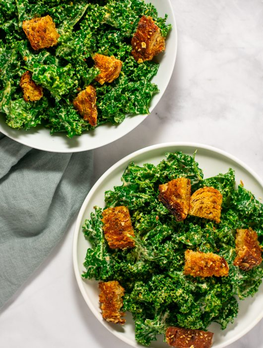 Overhead shot of two white plates with vegan kale caesar salad and croutons.