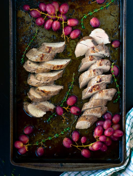 Overhead view of sliced balsamic pork tenderloin with grapes and fresh thyme on a sheet pan