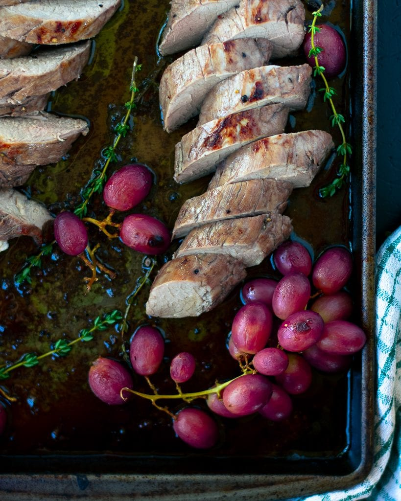 Overhead view of sliced balsamic pork tenderloin with grapes on a sheet pan