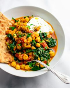 Overhead shot of a bowl of chickpeas with tomatoes, spinach, and lemon in a white bowl with pita bread.