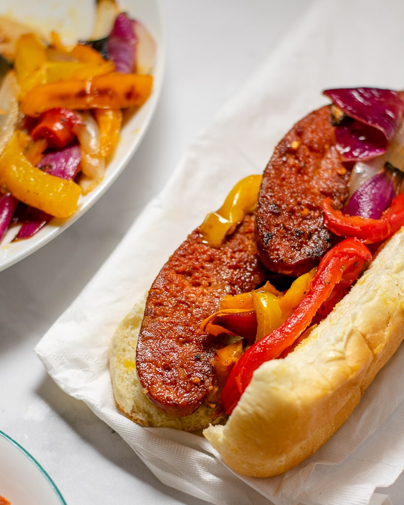 Grilled sausages in a soft bun with grilled peppers and onions