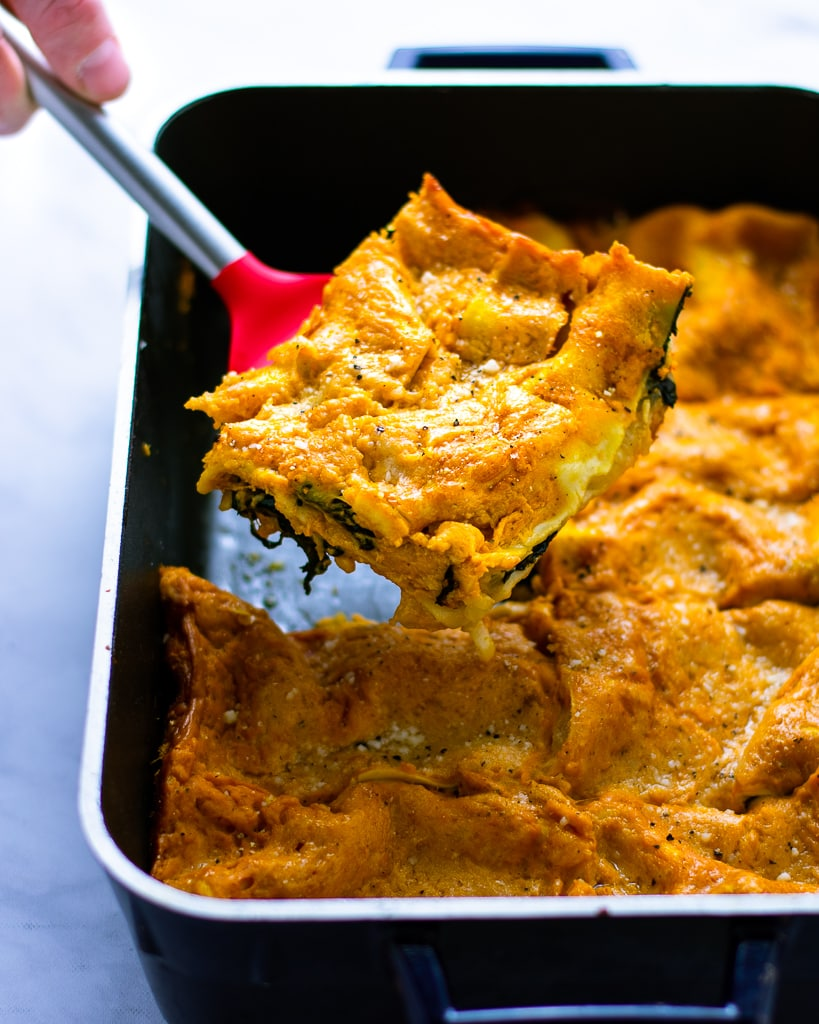 Piece of pumpkin spinach lasagna being lifted up from the casserole dish.