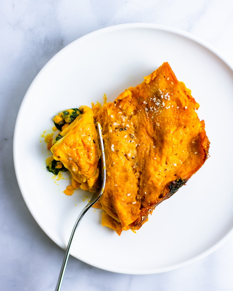 Overhead shot of a piece of pumpkin spinach lasagna on a white plate with a fork.