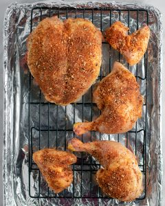 Raw chicken parts seasoned with a dry rub on a sheet pan,