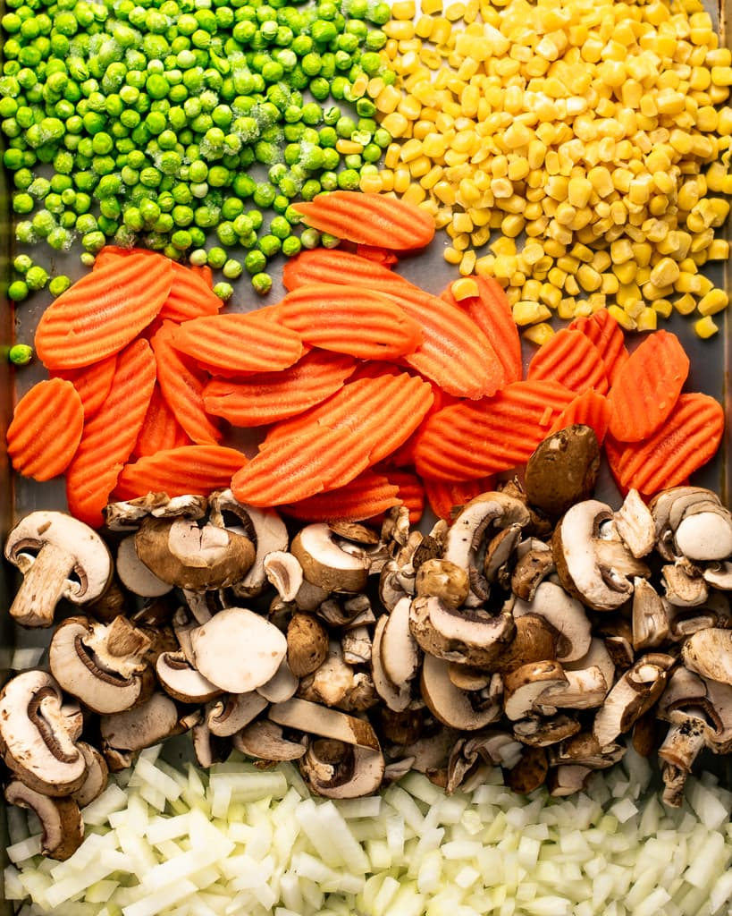 Peas, corn, carrots, mushrooms, and onions on a sheet pan.