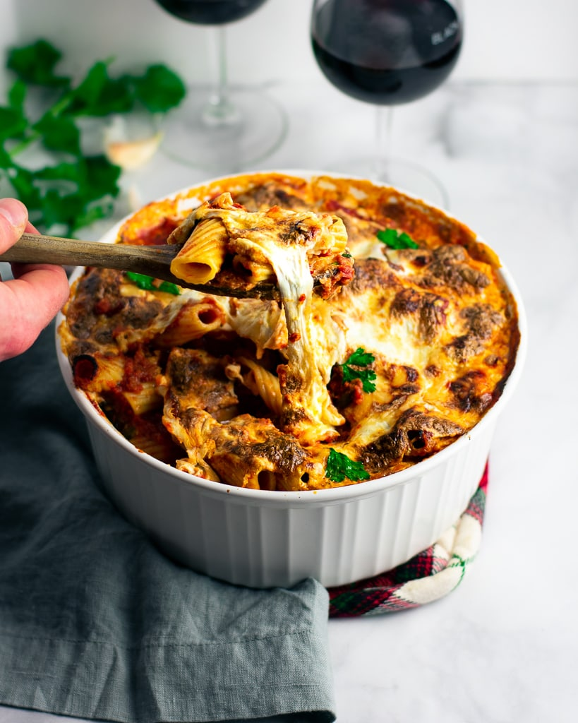 A wooden spoon lifting out a scoop of baked rigatoni with roasted vegetables in a white dish.