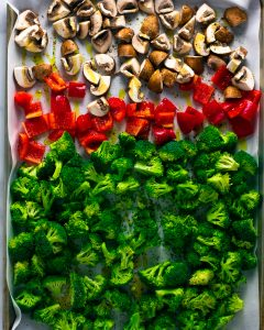 Overhead shot of a sheet pan with mushrooms, red pepper, and broccoli on it.