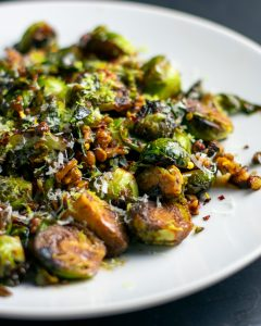 Up-close and side view of balsamic glazed brussels sprouts on a white plate.