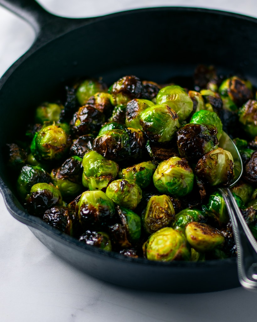 Up-close and side view of balsamic glazed brussels sprouts in a black cast iron skillet.